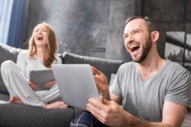 Frau und Mann haben Spaß am Laptop beim Lernen