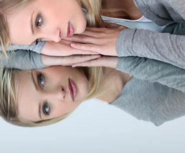 Spiegelneuronen - Lernen durch Imitation Frau blickt in den Spiegel