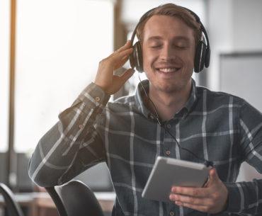Guter Sound beim Sprachenlernen ist wichtig - Mann hört Audio auf Tablet